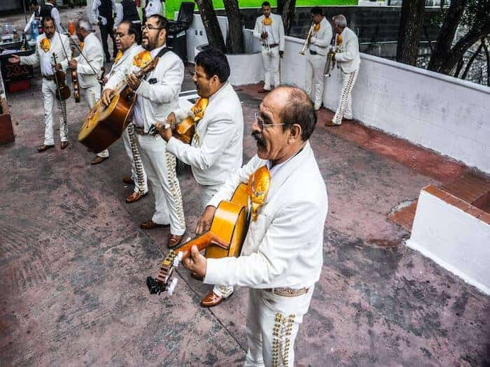 Mariachi musicians in white suites playing best Mariachi Songs to Request by Benjamin Patin on Unsplash