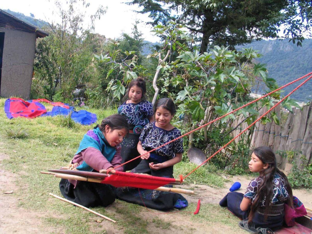 Tzotzil girls weaving on a backstrap loom in the Chiapas community.