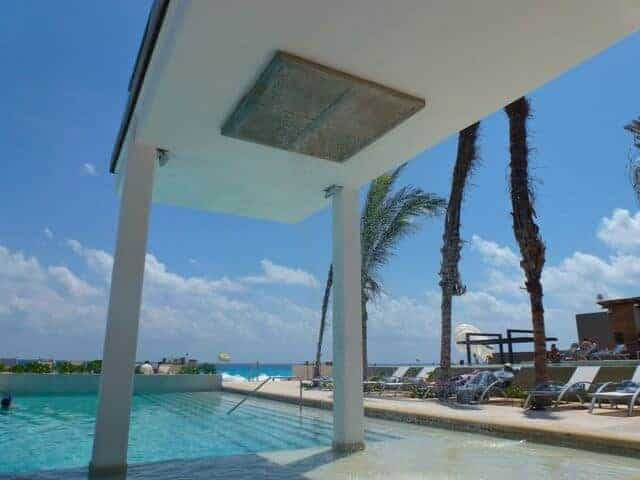 A large rain shower set over the Barefoot Pool at Secrets The Vine in Cancun.