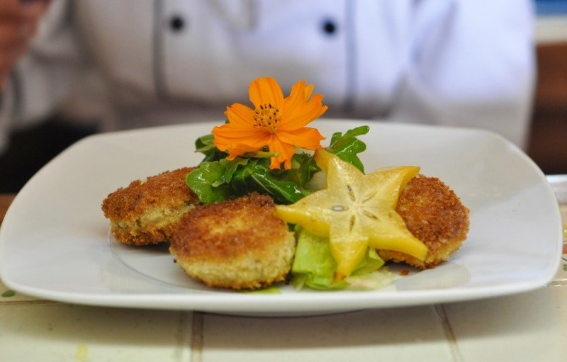Crab cakes with panko crumbs on a plate with orange flower in Puerto Vallarta.