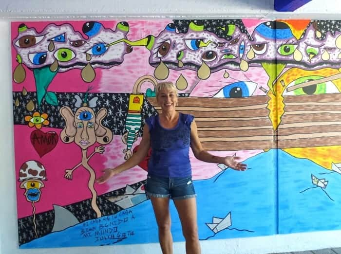 Massage therapist Beata Jesionowski in front of new mural by Julio Soto of Zicazteca Surf School