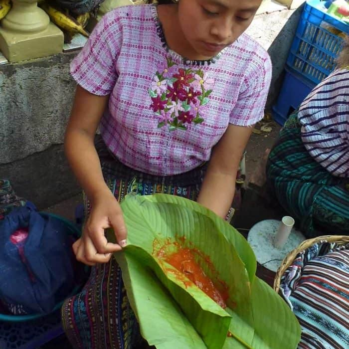 Vendor in the Santiago Atitlan market with patin wrapped in hoja de maxán