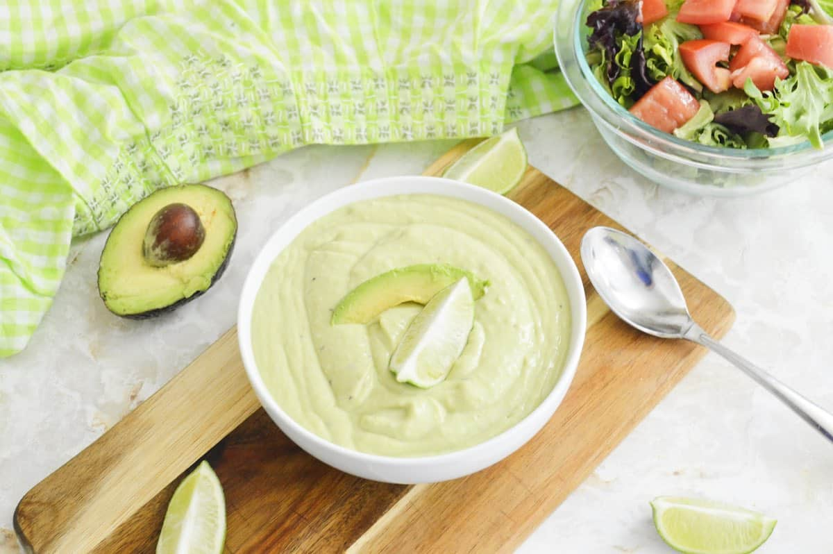 Avocado sauce in a white bowl on a wooden board.