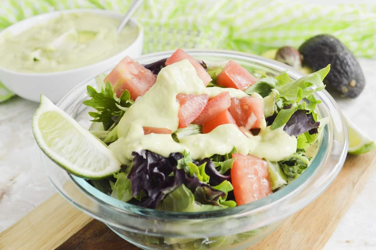 Close-up of avocado dressing on a green salad.