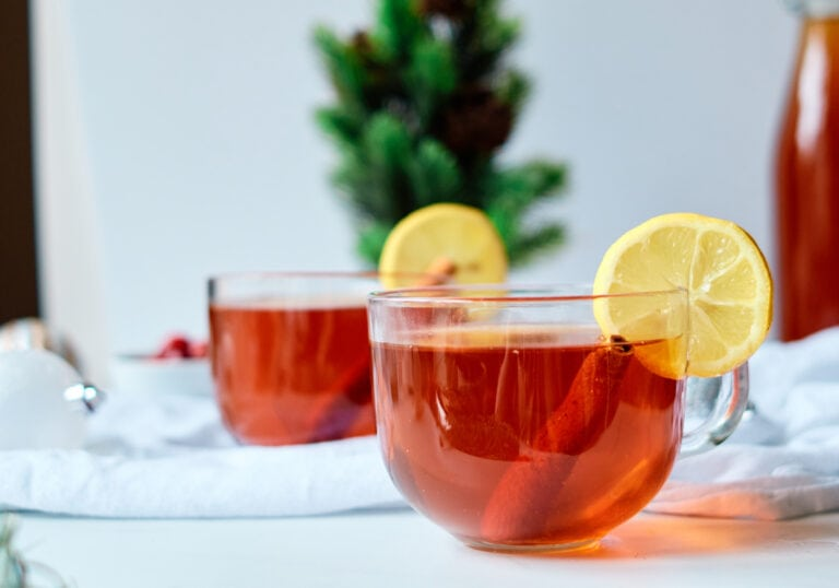 Hot Bourbon Toddy with lemon garnish on a white table.