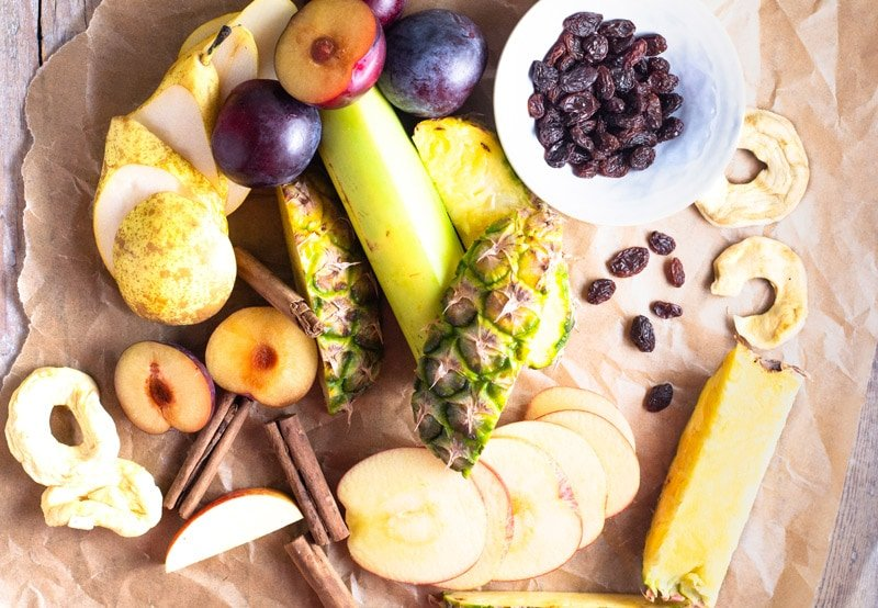 Ingredients for ponche de frutas includes dried apple, plantain, raisins, plums, cinnamon, pears and other fruit.