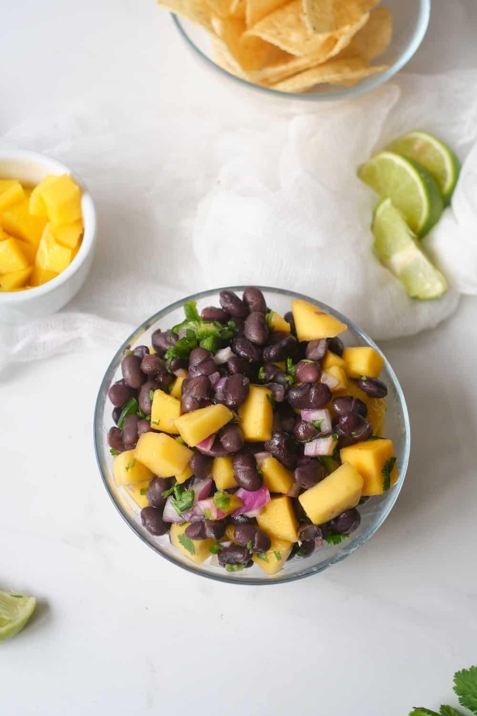 Overhead shot of black bean mango salad in a clear bowl.