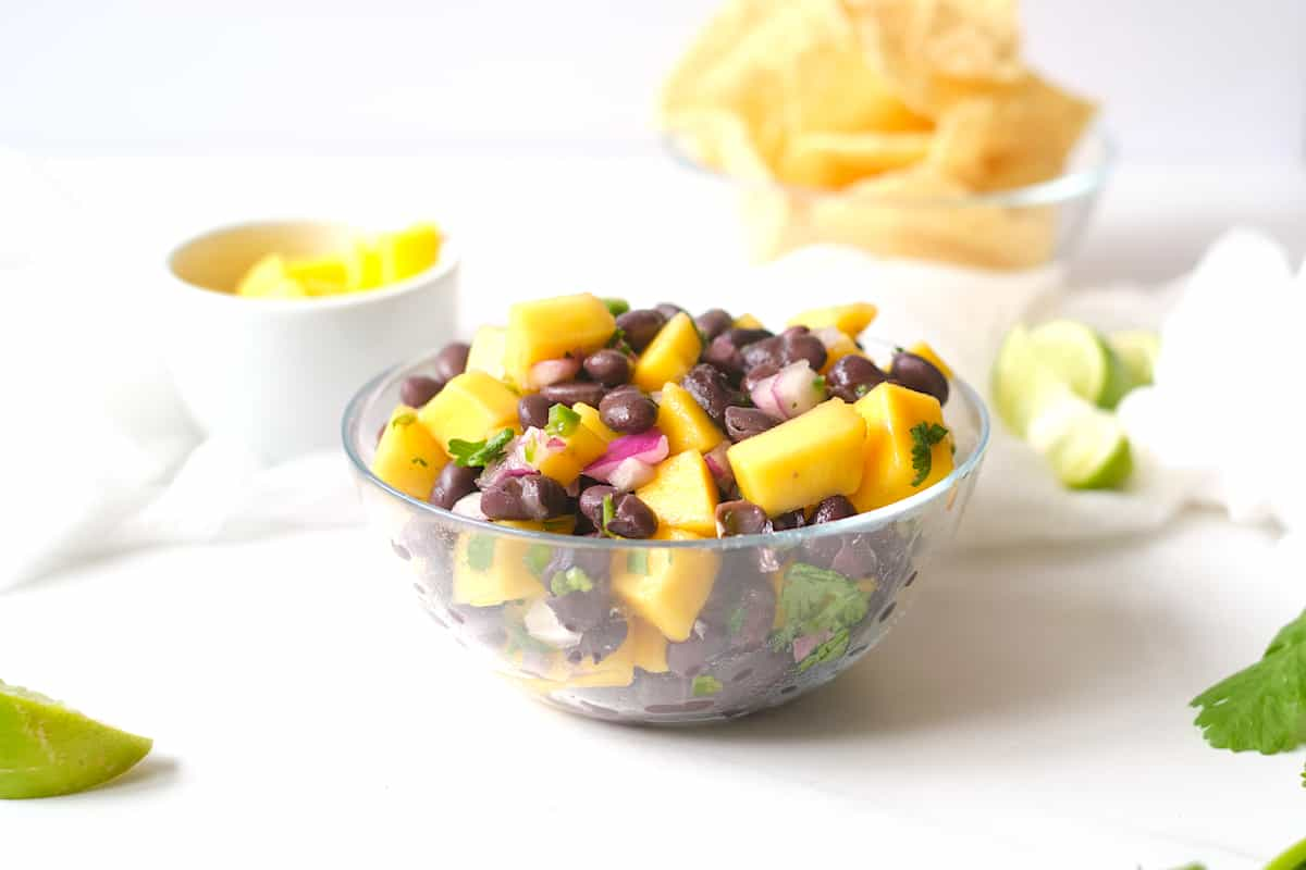 Mango black bean salad on a white table with limes and cilantro.