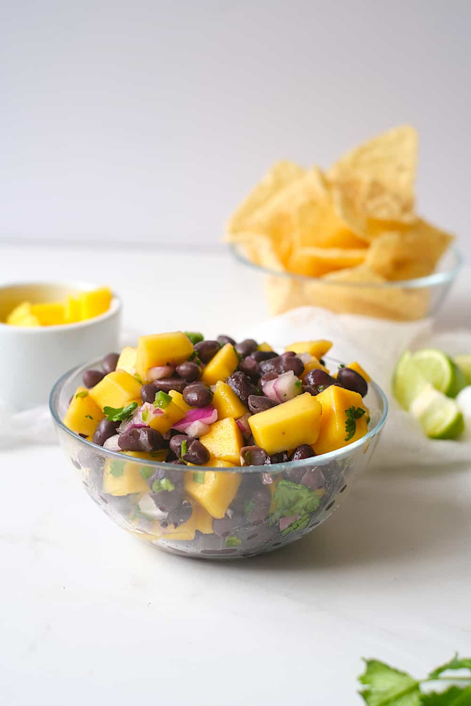 Portrait of Mango Black Bean Salad on a white table.