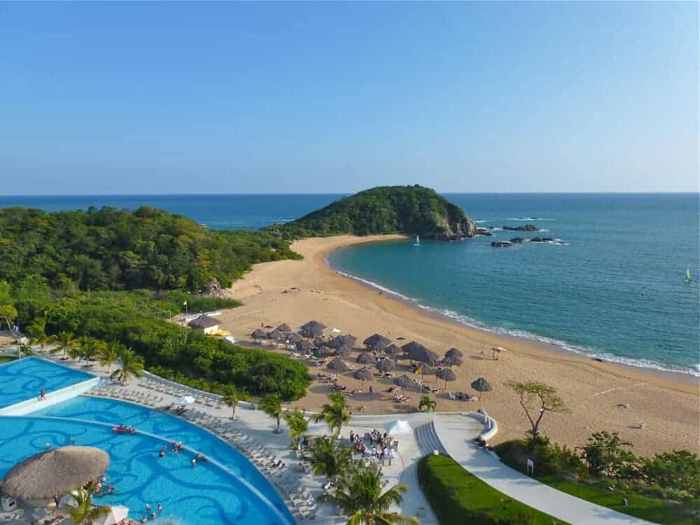 View of the swimming pool and beach at Secrets Resort in Huatulco in Oaxaca, Mexico.
