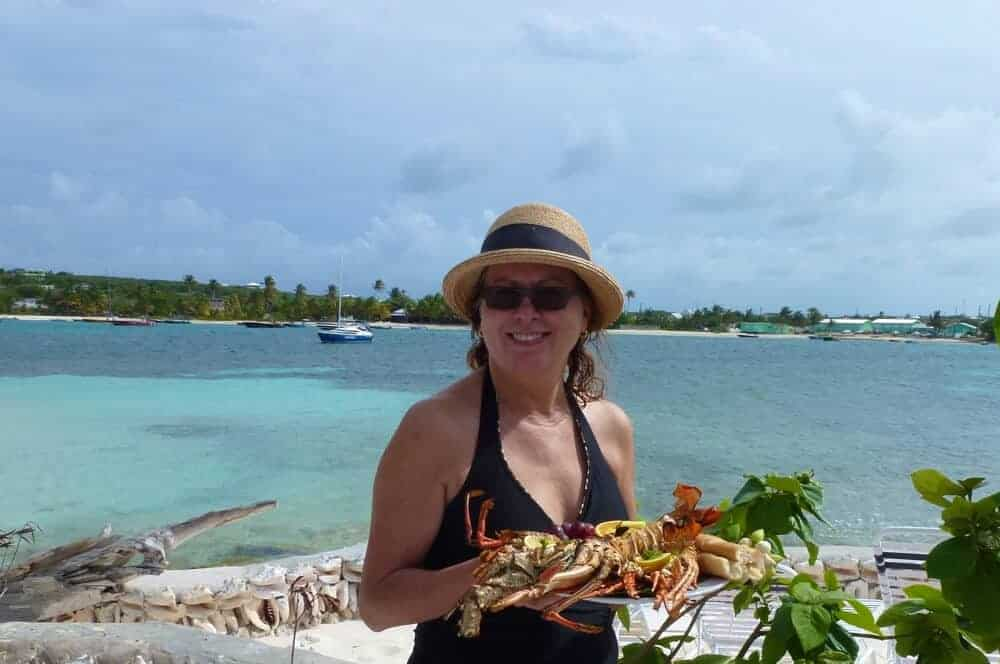 Woman holding a plate of grilled lobster at Scilly Cay, Anguilla.