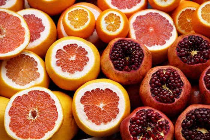 Sliced oranges and pomegranates. Photo by Israel Egío on Unsplash