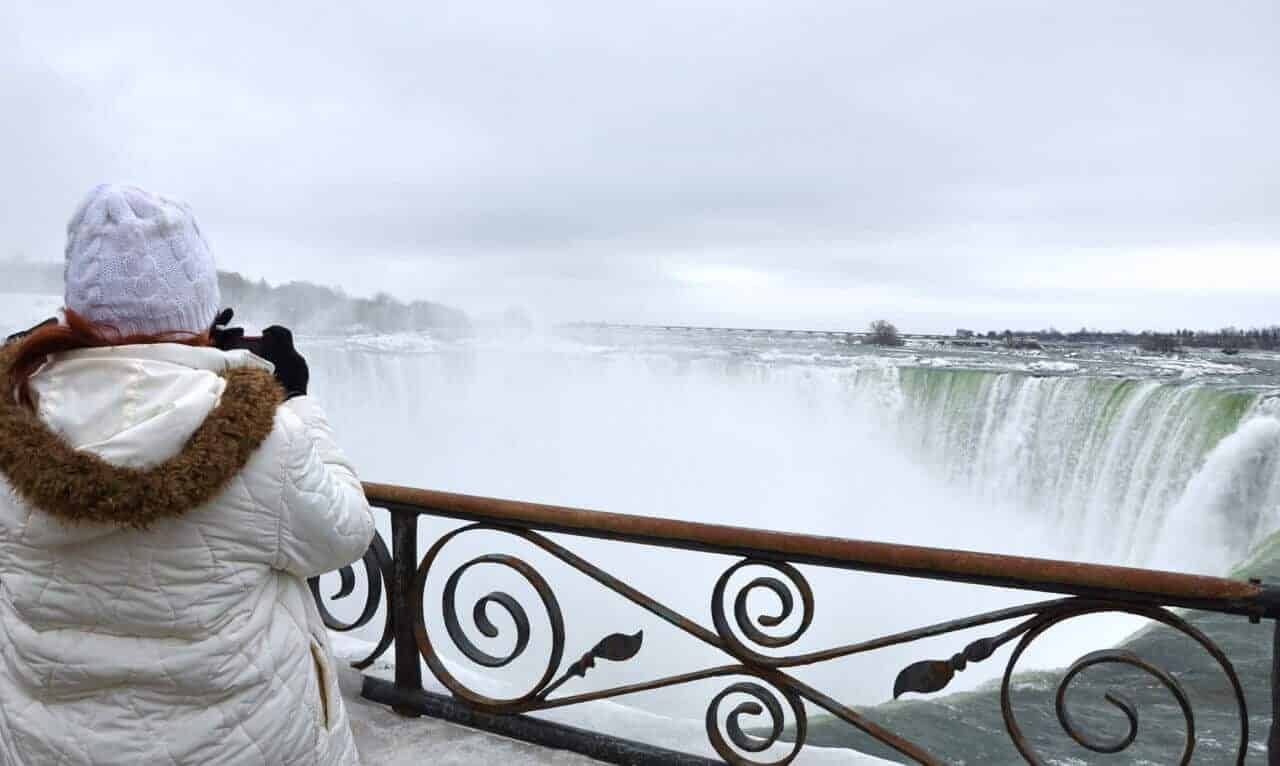 Tourist taking a photo of Niagara Falls in the winter.