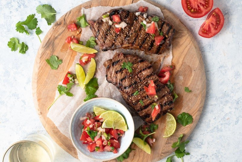 Beer and Balsamic Grilled Steak on a wooden board with fresh tomato salsa and lime