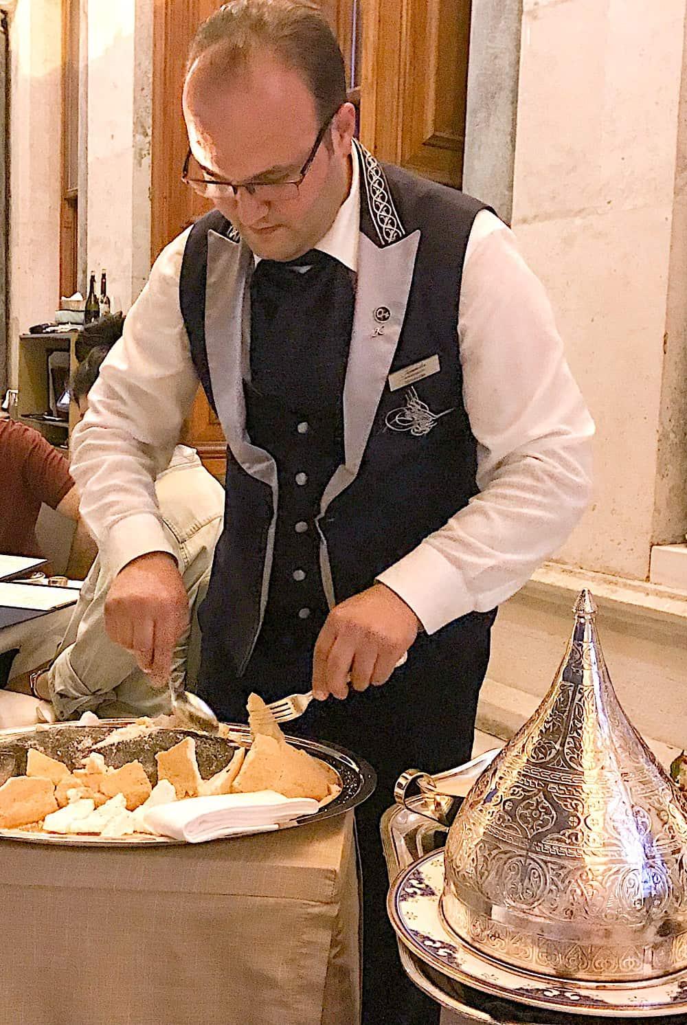 Server cutting open the sea bass in rock salt dough.