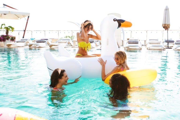 Group of women in a swimming pool with inflatable toys enjoying a girlfriends getaway together.