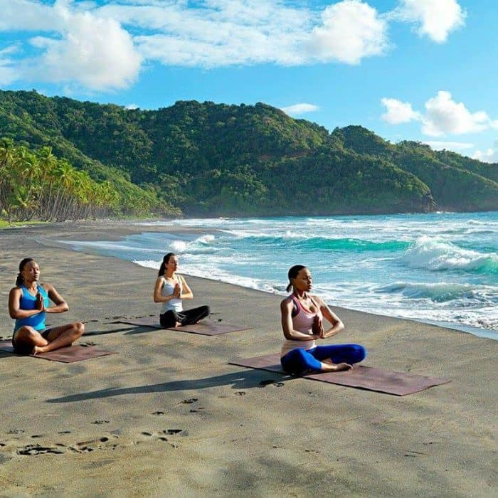 Women doing yoga on the beach during a girls getaway on at Rosalie Bay Resort Dominica