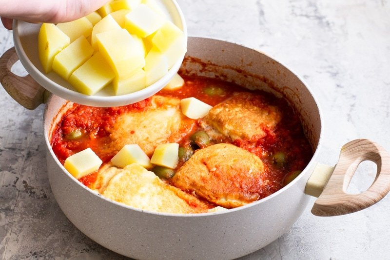 Add potatoes to the salt cod and tomato sauce