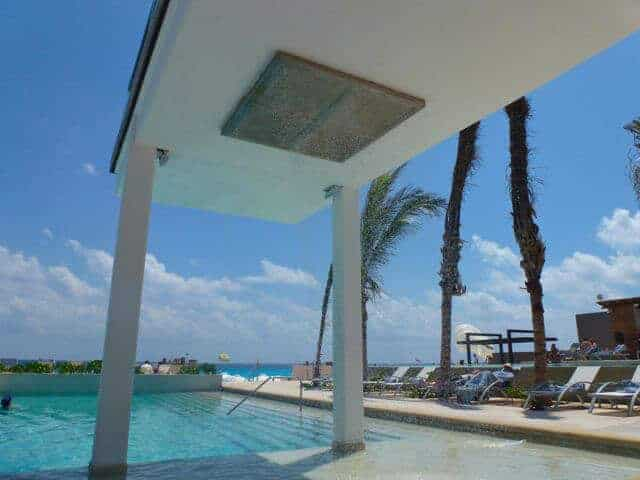 Soak under the incredible rain shower at the Barefoot Pool at Secrets The Vine Resort & Spa in Cancun