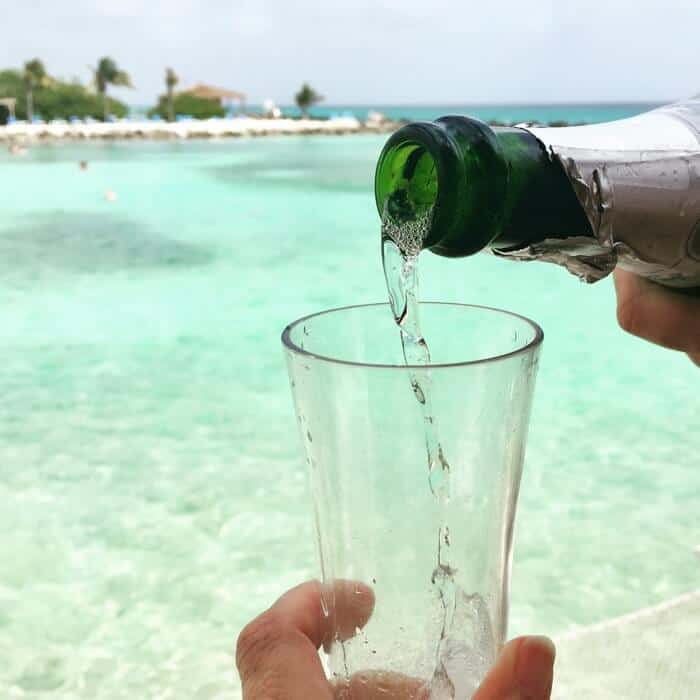 Champagne being poured into a glass during a luxury VIP experience at a private cabana at Renaissance Aruba Private Island.