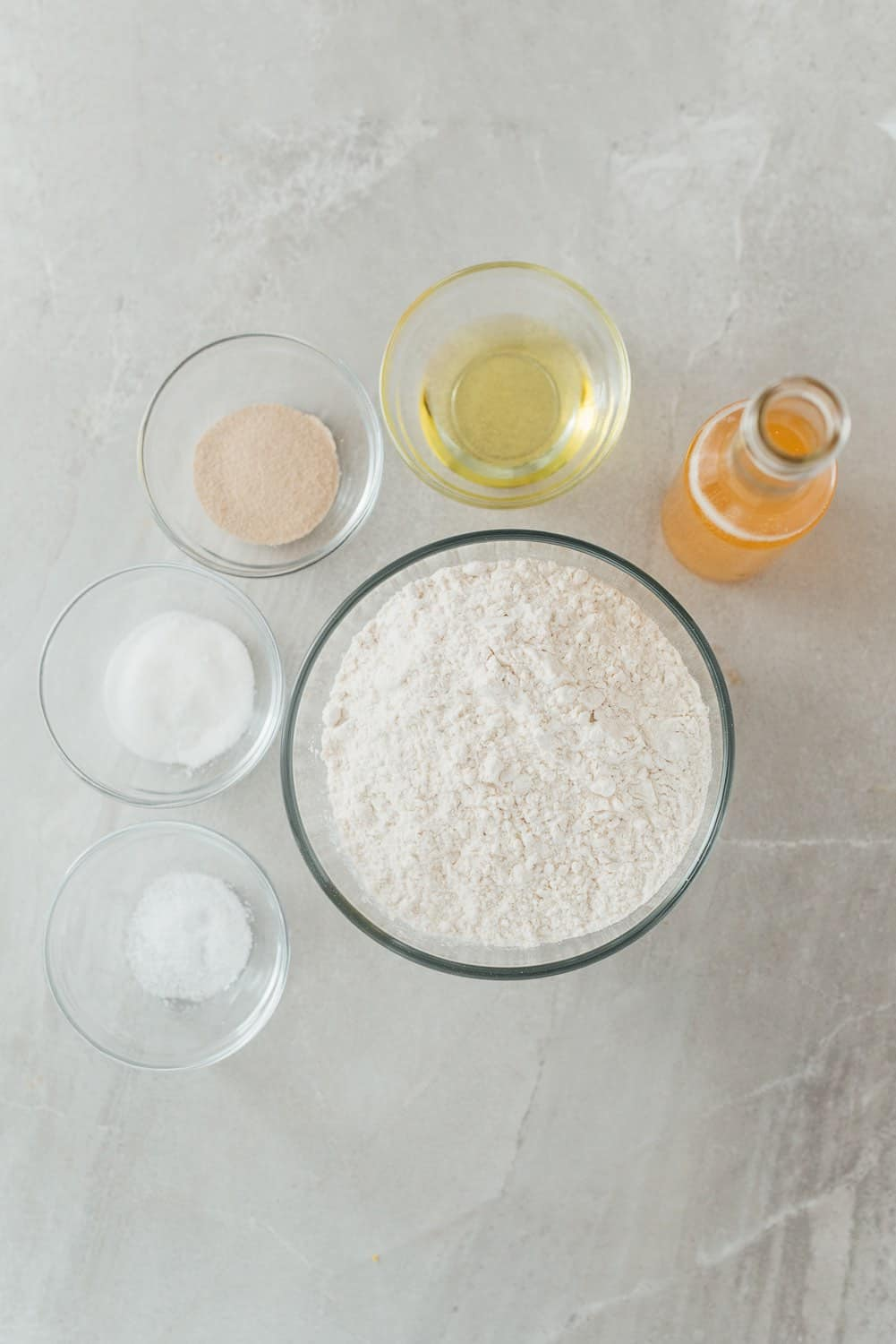 Ingredients for making beer pizza dough including salt, white sugar, olive oil, all-purpose flour, beer and yeast.
