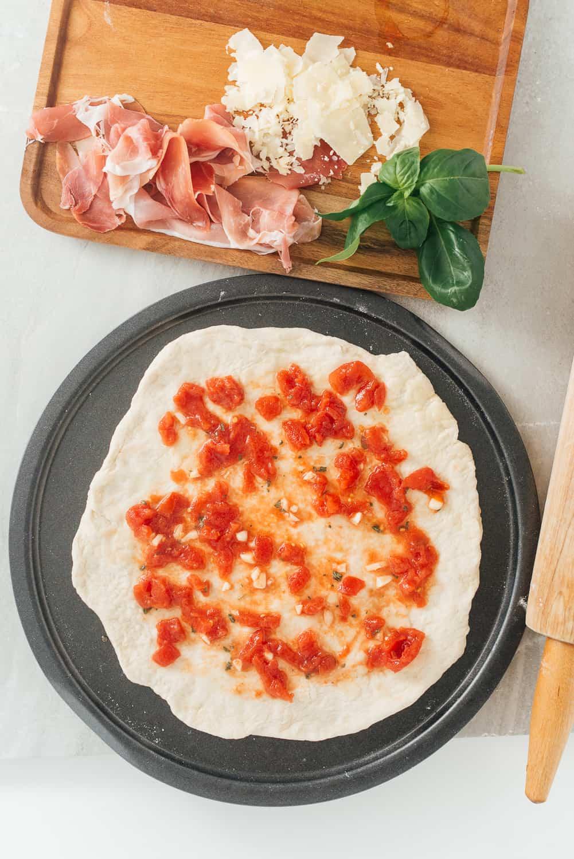 Spread the pizza sauce on a dough.
