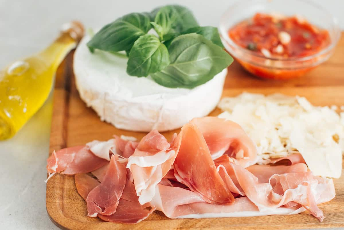 Prosciutto, brie, basil and parmesan toppings for pizza.