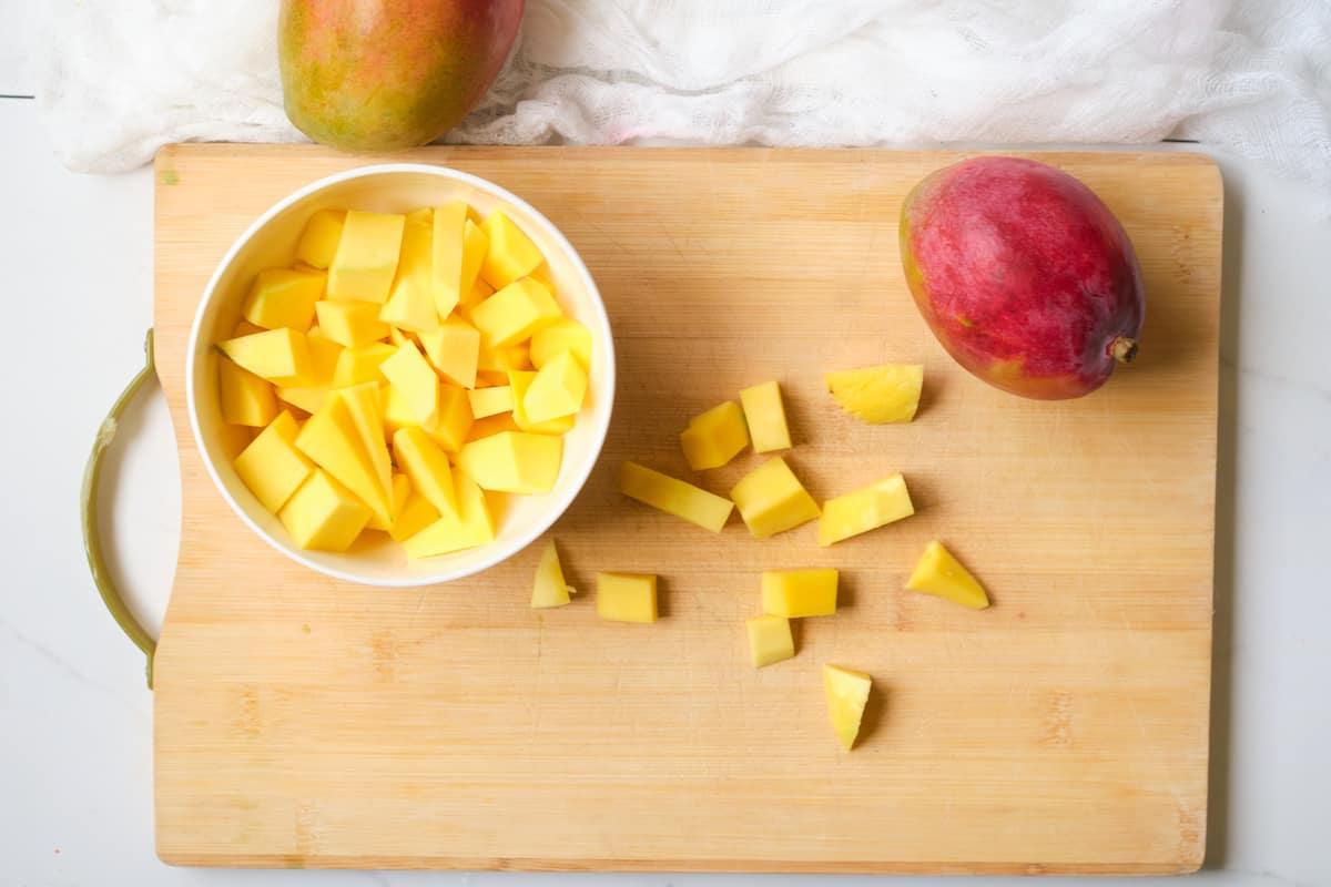 Chopped mango on a wooden board.