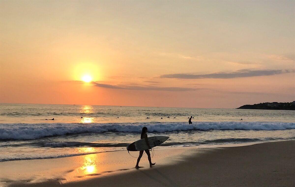 Surfer at sunset on the beach in Puerto Escondido Oaxaca.
