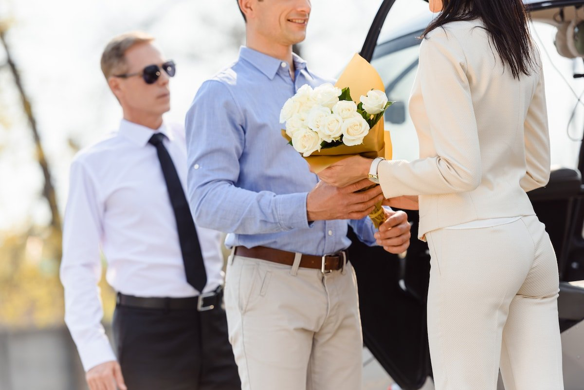 A young man giving flowers to a woman in front of a helicopter.