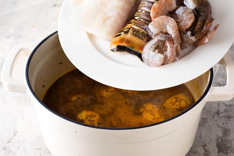 Adding seafood to tapado Guatemalan seafood soup