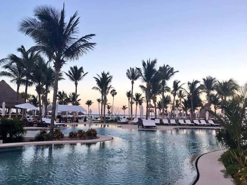 View of the swimming pool with palm trees at Secrets Akumal Riviera Maya. (Credit TheDownLo)