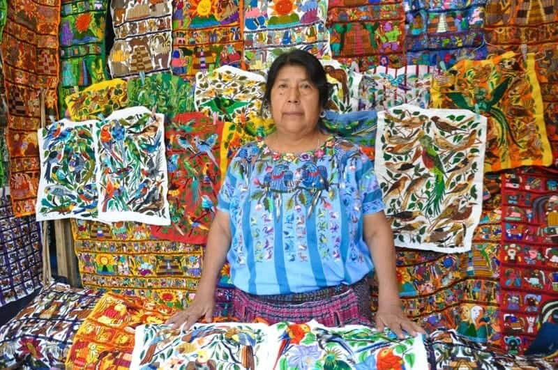 Female vendor at embroidery stand in Chichicastenango, Guatemala.