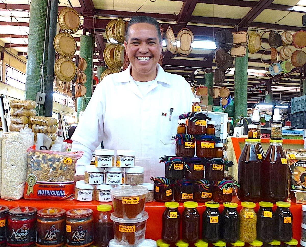 Smiling vendor at a stall at Mercado San Juan in Mexico City.