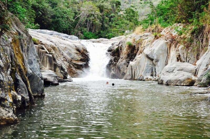 Two men swimming in waterfall at Pasabien balneario in Zacapa, Guatemala.