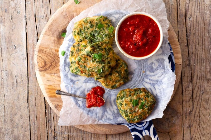 Green Bean Fritters or Tortitas de Ejotes Guatemalan on a wooden tray with salsa.