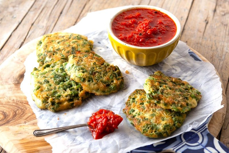 An appetizer presentation of small green bean pancakes on a wooden board with tomato salsa. ers