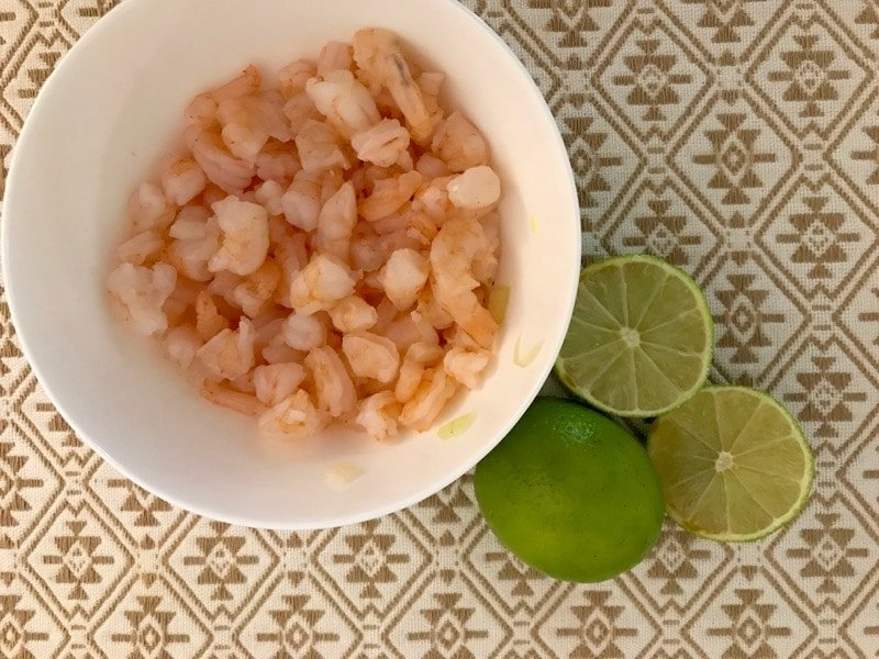 Cooked shrimp for ceviche with limes.
