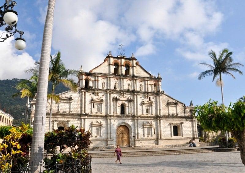Woman walking past Church of St. Francis de Assisi in Panajachel Guatemala.