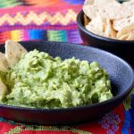 Easy Guatemalan Guacamole in an earthen bowl on a Mayan weaving