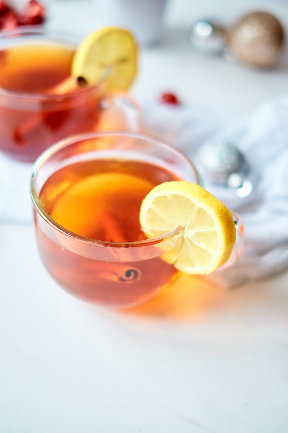 A clear mug of hot bourbon toddy with lemon on a table.