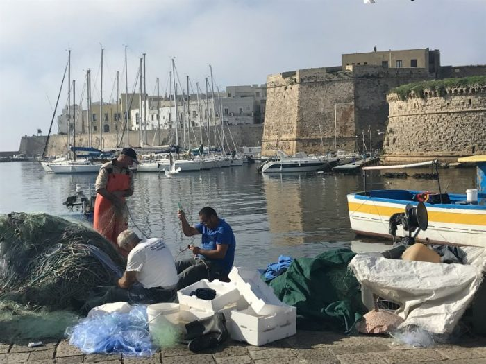 Fishermen in the harbour in Gallipoli in Puglia, Italy