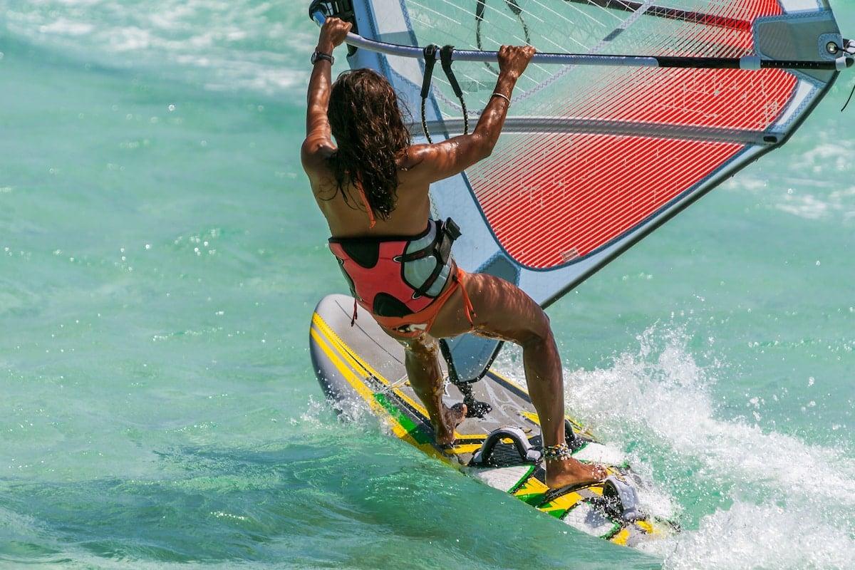 Woman windsurfing in clear blue waters.