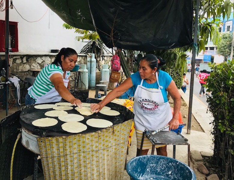 Women making tortillas de maize, a top food in Puerto Escondido Mexico.