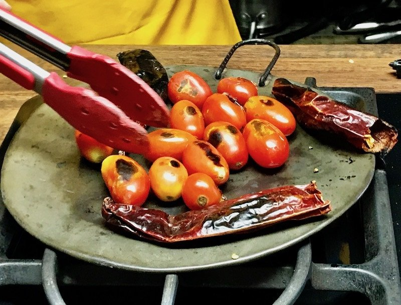 Charring tomatoes in a comal in Guatemala
