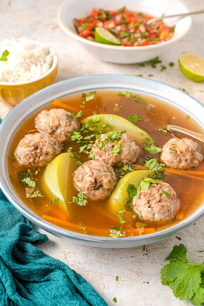Sopa de Albondigas Guatemalan Meatball soup in a white bowl with rice on the side.