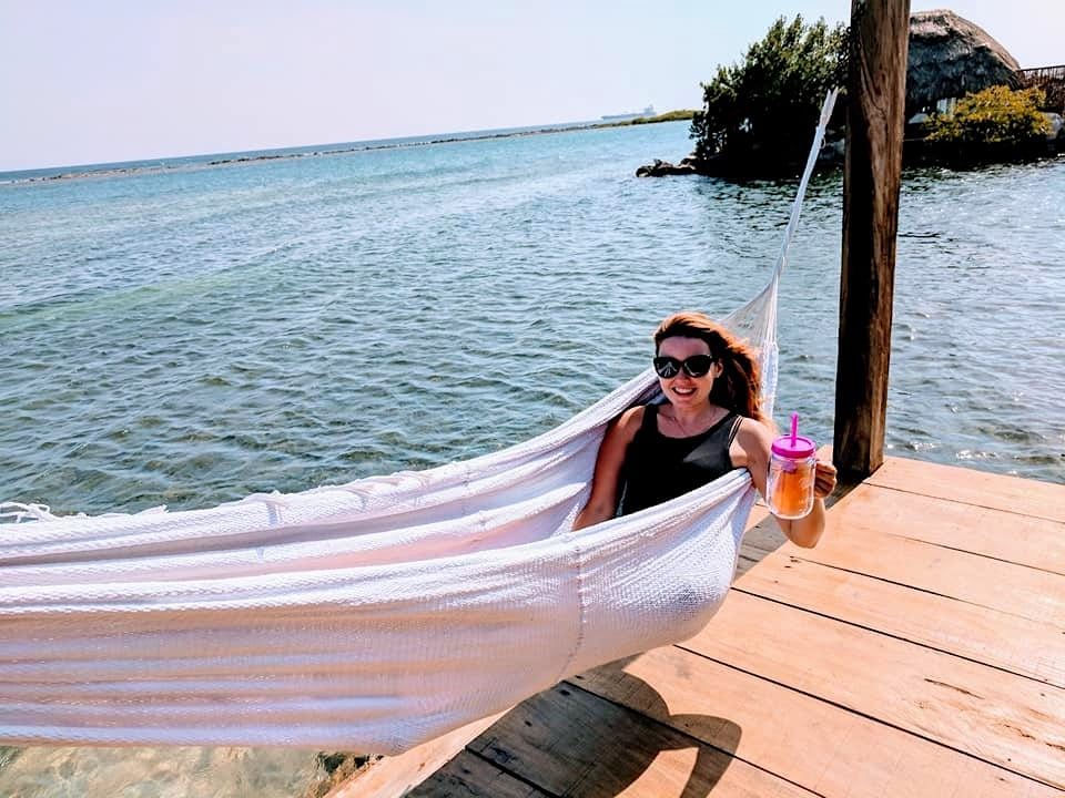 Woman in a hammock with a cocktail