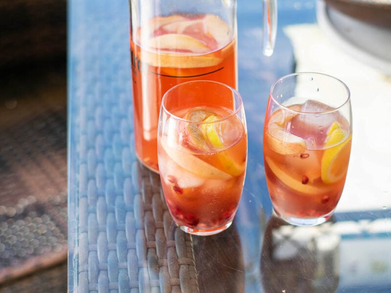 Bourbon punch pitcher and glasses with ices on patio table.
