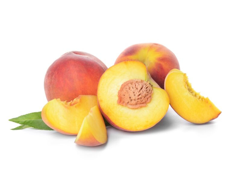 Whole and cut peaches on white background.