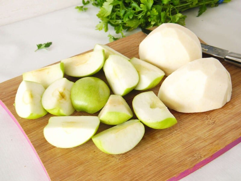 Chopped apple and jicama on a wooden cutting board ready to be grated.